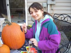 Thumbnail of Photograph: Delaware, Ohio, 2008, Olena Dyedukh drawing on pumpkin.