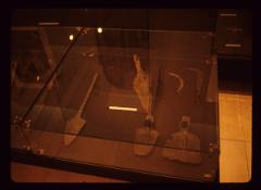 Thumbnail of A glass case with an arrowhead, a spearhead and several other metal items