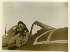 Thumbnail of John Glenn sitting in the cockpit of his F4U Corsair