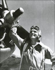 Thumbnail of John Glenn posing in front of his F4U Corsair