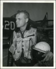 Thumbnail of John Glenn in front of his F9F Panther holding his flight helmet during the Korean War