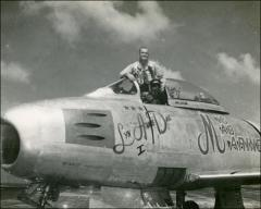 "Thumbnail of John Glenn standing in the cockpit of his ""MiG Mad Marine"""