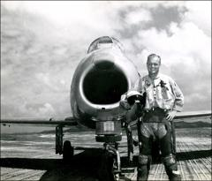 "Thumbnail of John Glenn standing in front of his ""MiG Mad Marine"""