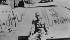 "Thumbnail of John Glenn standing sitting on the wing of his ""MiG Mad Marine"""