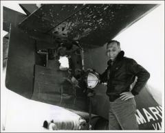 Thumbnail of John Glenn standing beside the damage to the tail of his F9F Panther from antiaircraft fire