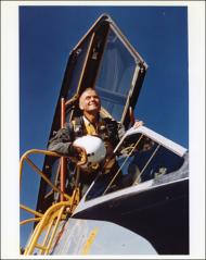 Thumbnail of John Glenn sitting astride the cockpit of a jet aircraft at the U.S. Navy Test Station at Patuxent River, Maryland