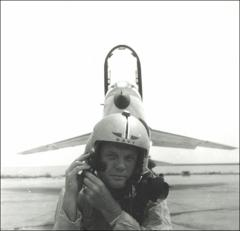 Thumbnail of John Glenn posing in front of his F8U-1P Crusader adjusting helmet straps