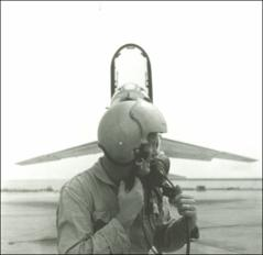 Thumbnail of John Glenn posing in front of his F8U-1P Crusader adjusting helmet straps, side view