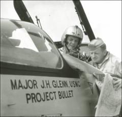 Thumbnail of John Glenn sitting in the cockpit of his F8U-1P Crusader looking at a map