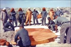 Thumbnail of Project Mercury astronauts watching instructors, during desert training at the USAF Survival School