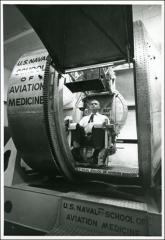 Thumbnail of John Glenn sitting in a machine used to test motion sickness