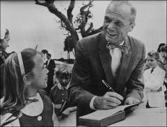 Thumbnail of John Glenn signs his autograph for a young girl