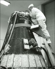 Thumbnail of John Glenn inspects the top of a Mercury spacecraft