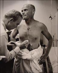 Thumbnail of Dr. Douglas attaches medical sensors to John Glenn during the pre-launch preparations