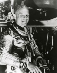Thumbnail of John Glenn poses beside Friendship 7