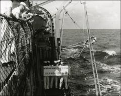 Thumbnail of Sailors on the U.S.S. Noa hold a sign welcoming astronaut John Glenn