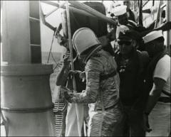 Thumbnail of John Glenn stands upon the deck of the U.S.S. Noa