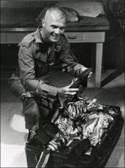 Thumbnail of John Glenn packs up his spacesuit