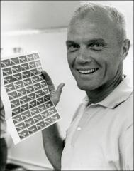 Thumbnail of John Glenn holds a sheet of Project Mercury U.S. Postage stamps