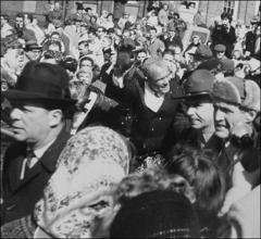 Thumbnail of John Glenn waves at the crowds lining Main Street during the New Concord, Ohio parade