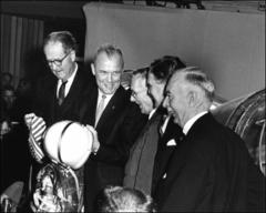 Thumbnail of John Glenn holds up his spacesuit and helmet during ceremonies presenting Friendship 7 to the Smithsonian