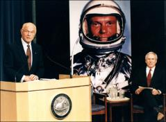 Thumbnail of John Glenn speaking at the NASA press conference announcing his return to space