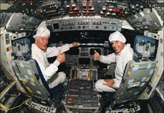 Thumbnail of John Glenn and Stephen Oswald sitting in the flight deck of Space Shuttle Discovery