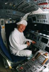 Thumbnail of John Glenn sitting in the flight deck of Space Shuttle Discovery