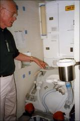 Thumbnail of John Glenn examines a mock up of the toilet facilities in a space shuttle
