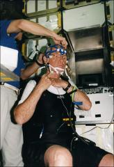 Thumbnail of John Glenn gets fitted for head harness to monitor his sleep