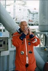 Thumbnail of John Glenn talks on a launch pad telephone