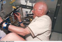 Thumbnail of John Glenn working with the OSTEO experiment console during STS-95
