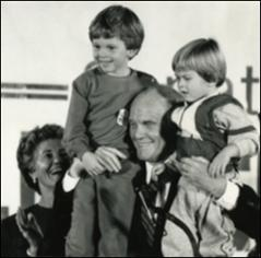 Thumbnail of John Glenn holds up his two grandchildren as Annie Glenn applauds