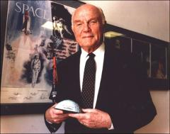 Thumbnail of John Glenn holding a model of the Friendship 7 spacecraft, 1998