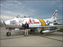 "Thumbnail of John Glenn next to a restored F-86 Sabre with the markings of the ""MiG Mad Marine"" jet he flew in the Korean War"