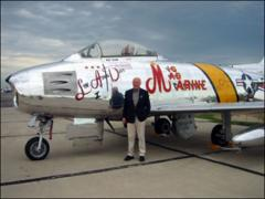 "Thumbnail of Close-up of John Glenn next to a restored F-86 Sabre with the markings of the ""MiG Mad Marine"" jet he flew in the Korean War"