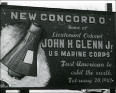 "Thumbnail of Sign on the outskirts of New Concord, Ohio, reading ""Home of Lieutenant Colonel John H. Glenn Jr. - U.S. Marine Corps - First American to orbit the earth, February 20, 1962"""