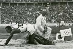 Thumbnail of Jesse Owens landing after his Olympic and world record broad jump, 1936