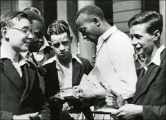 Thumbnail of Jesse Owens signing autographs, 1936