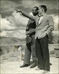 Thumbnail of Jesse Owens stands with unidentified man during trip west for NCAA Championship, 1935