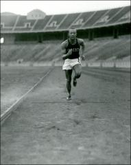 Thumbnail of Jesse Owens, shown full-length, running towards camera at Ohio Stadium, 1934