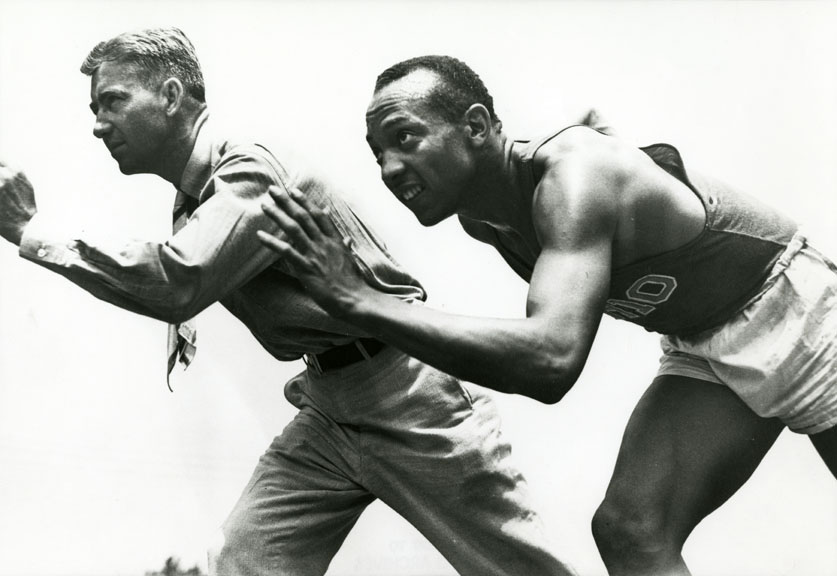 jesse owens and coach larry snyder posed in a running position