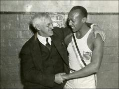 Thumbnail of Jesse Owens wearing his Olympic track uniform and posed with Charles Riley, 1936