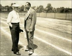 Thumbnail of Jesse Owens and Charles Riley speaking while standing on the track, 1937