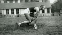 Thumbnail of Jesse Owens crouched in the starting position, side view, 1935