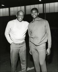 Thumbnail of Jesse Owens poses for a photo with an athlete, 1968