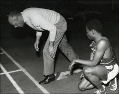 Thumbnail of Jesse Owens shows a young student athlete how to start a track race, 1968