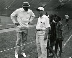 Thumbnail of Jesse Owens talks with a coach and young athletes at the Jesse Owens Track Meet, 1969