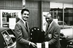 Thumbnail of Jesse Owens presents a man with a flag, 1960s