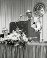 Thumbnail of Jesse Owens on stage at a podium during the National Association of Collegiate Directors of Athletics event, 1960s